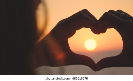 Portrait of a girl from the hands made a heart shape at sunset, on the sea, against an orange background. Concept: love to relax at sea, freedom, love, life style, evening sunset, beach, summer, sun.