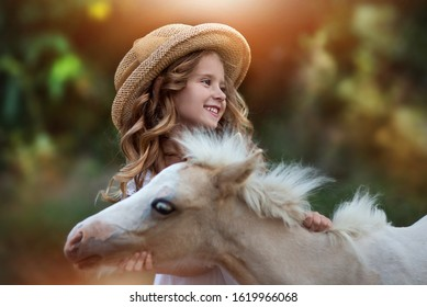 Portrait of a girl in a hat with a white pony in the sunlight
