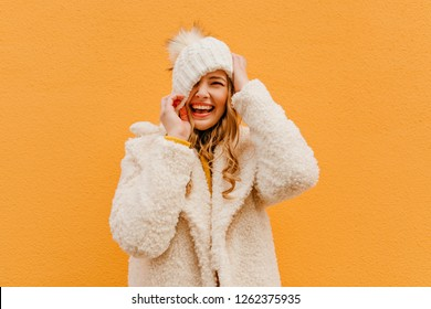 Portrait of girl having fun on isolated background in woolen coat. Blonde puts hat on face