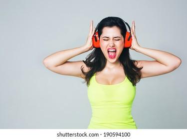 Portrait of a girl in headphones. She screams
