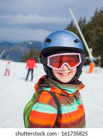 Portrait of girl in helmet and ski goggles on a sunny day in the mountains