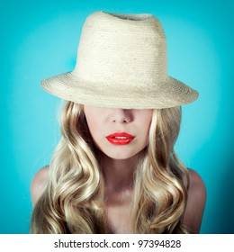 Portrait of a girl hiding her eyes behind a straw hat