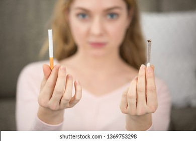 portrait of girl holding a bought and a hand-rolled cigarette