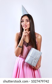 Portrait of girl holding gift box in hands . Woman in pink dress in her birthday party