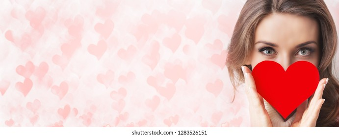 Portrait of girl holding red paper heart over many pink hearts background
