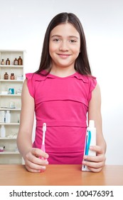 Portrait of girl holding toothbrush and tooth paste.