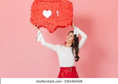 "Portrait of girl with interest looking at huge """"like"""" sign from Instagram. Brunette in red skirt posing on pink background"