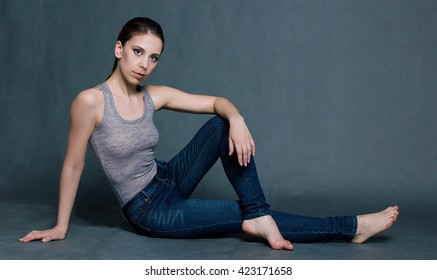 Portrait of a girl with jeans on a gray background