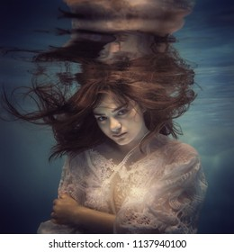 Portrait of a girl in a lace dress under the water