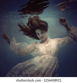 Portrait of a girl in a lace dress under water.