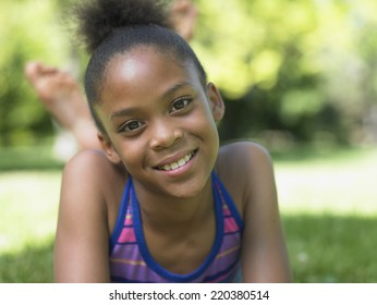 Portrait of girl laying in grass smiling