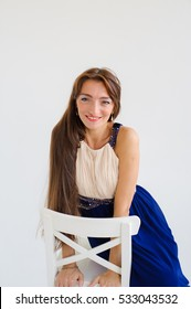 portrait of a girl with long brown hair.with jewelry.in a long dress on a white background. sitting on a chair.
