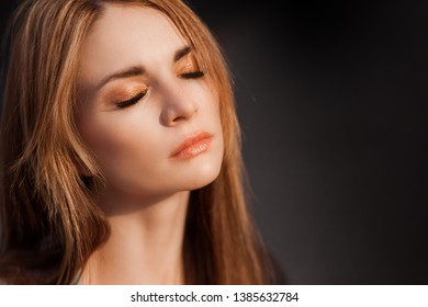 Portrait of a girl with long hair on a dark background. Copy space