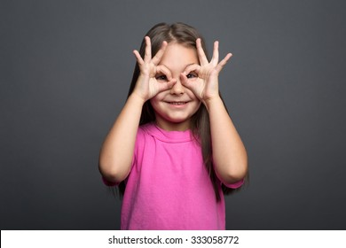 Portrait of a girl looking through her fingers