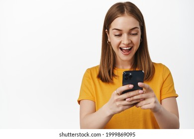 Portrait of girl looks surprised and excited at smartphone screen, receive pleasant notification, watching video on mobile phone, cellular internet, white background