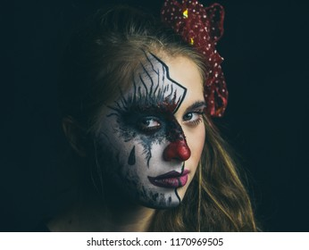 Portrait of a girl in makeup. Halloween, the face of a girl is a doll, the floor of a face is dead