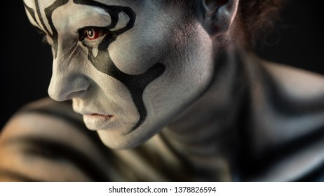 portrait of a girl in the makeup of a mystical creature of black white color with fiery red eyes, art image