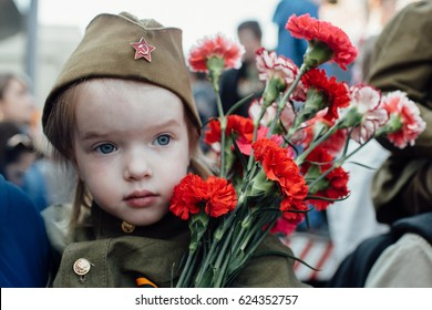 Portrait of a girl in military uniform with flowers on May 9