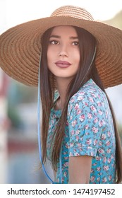 Portrait of a girl model with a big straw hat