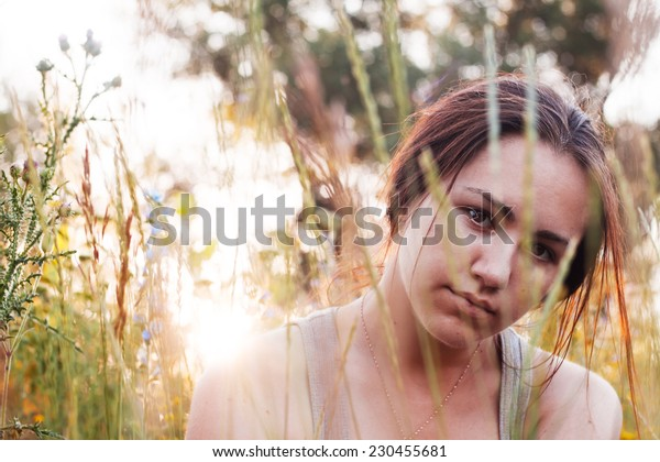 Portrait of girl in nature. Beautiful brunette and summer plants, flowers. Backlight