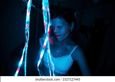 Portrait of a girl in a neon blue room with a garland in his hand holds a banana speaks on it