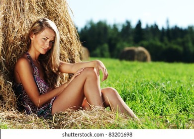 portrait of a girl next to a stack of hay