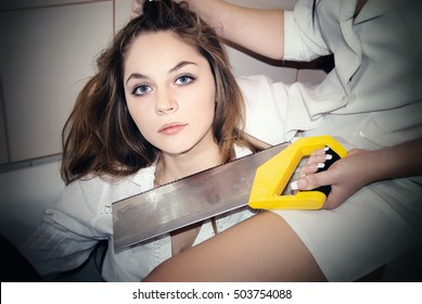 Portrait of a girl. Nurse holding her by the hair and wants to cut off the head saw. Staged terrible scene