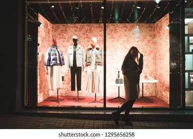 Portrait of a girl on the background of a fashion store showcase. Girl walks at the window of a fashion shop with dummies at night.