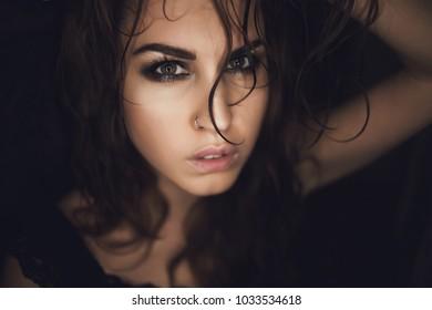 Portrait of girl on black background, nose ring, wet hair
