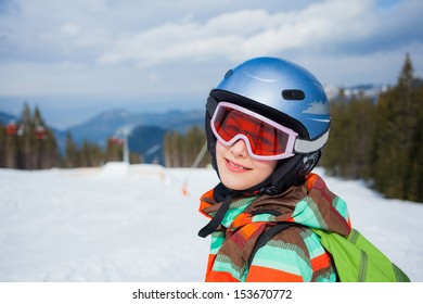 Portrait of girl on skis in helmet and ski goggles on a sunny day in the mountains