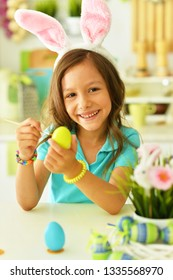 Portrait of girl painting eggs for Easter holiday