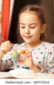 Portrait of girl painting traditional easter eggs at home