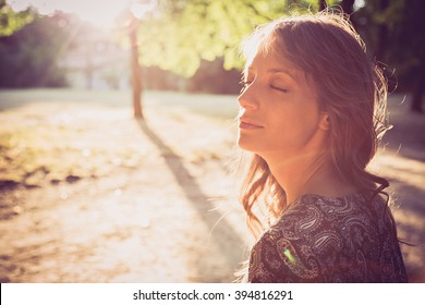 Portrait of a girl in park with closed eyes. Sun glare