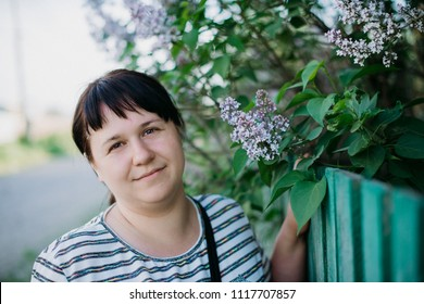Portrait of a girl in a park near a lilac bush
