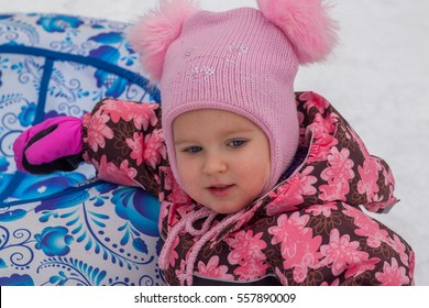 Portrait of a girl in a pink hat. Blue-eyed girl in a hat with pompoms and a pink jacket sitting near the blue tubing in the snow. Winter walk