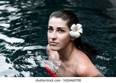 Portrait of a girl in the pool with a flower