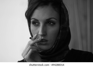 Portrait of a girl for a portfolio with a handkerchief tied by Hollywood and cigarette emotions fashion habits style
