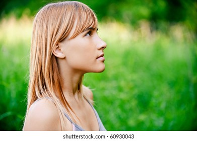 Portrait of girl in profile against green summer nature.