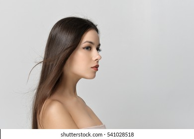Portrait of girl in profile. Beautiful woman with bare shoulders has a clean well-groomed skin and long straight hair. Close-up portrait against a light gray background.