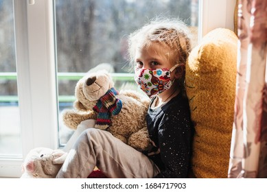 Portrait of a girl in a protective mask . A sick child wearing a protective mask. Patient isolated in house to prevent infection. Coronavirus. Teaching your child preventive measures against covid-19