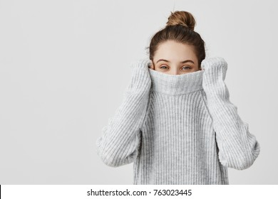 Portrait of girl pulling her trendy sweater over head having fun. Woman with tied hair in topknot being childish disappearing in her clothes looking from underneath. Happiness concept