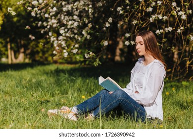Portrait of  girl reading a book in the park.