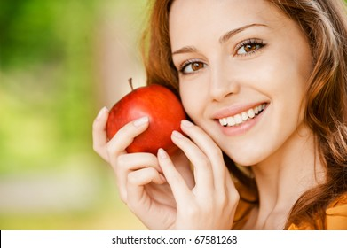 Portrait of girl with red apple against green grass.
