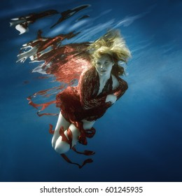 Portrait of a girl in a red dress underwater