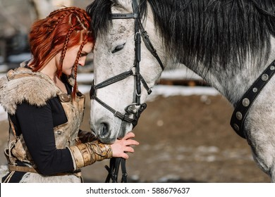 portrait of a girl with red hair in a Viking outfit with a horse.