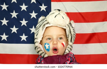 Portrait of a girl in a red jacket and white hat, with the US flag a bright background.
