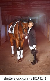 Portrait of a Girl rider near her brown horse in stable. get ready for riding