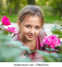 portrait of a girl in a rose bush in the park