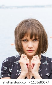 Portrait of a girl with a short haircut on the background of water