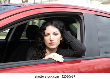 Portrait of the girl sitting in red car